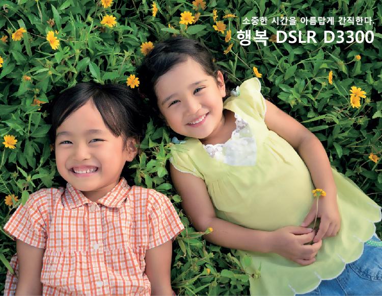 사진: 두 여자 아이가 노란꽃들이 핀 푸른 풀밭에 누워 있는 이미지 오른쪽 상단에 '일안 리플렉스 카메라로 행복하게 소중한 시간을 아름답게 간직한다'라는 문구가 적혀있음