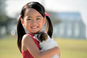 사진:강아지를 안고 있는 여자아이 모습