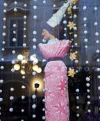 쇼윈도에 걸려 있는 꼬깔 모자를 쓰고 자수옷을 입은 인형을 촬영한 모습입니다.