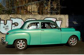 에메랄드빛의 차가 담벼락에 세워져 있는 사진