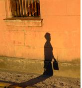 노을진 무렵 가방을 든 남자의 그림자가 벽에 그리워진 사진